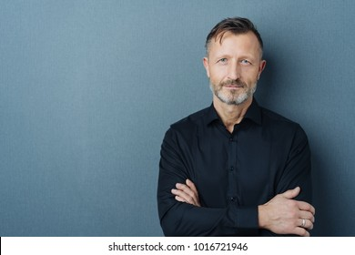 Serious middle-aged man with folded arms and a deadpan expression posing in front of a grey background with copy space - Shutterstock ID 1016721946