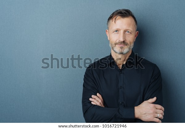 Serious middle-aged man with folded arms and a deadpan expression posing in front of a grey background with copy space