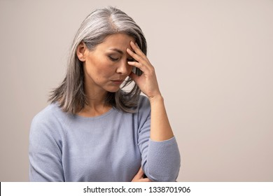 Serious Middle-Aged Woman Touches Her Forehead While Thinking About Something. Upset Asian Woman With Grey Hair Stands And Touches Her Forehead Thinking.