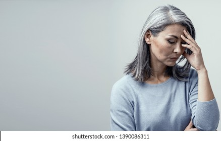 Serious Middle-Aged Woman Touches Her Forehead and Thinking About Something. Upseted Asian Woman With Grey Hair Stands And Touches Her Forehead Thinking. Right Side Portrait
