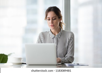 Serious millennial female worker busy at laptop in modern office, focused woman boss or ceo using computer writing business emails or browsing internet, businesswoman work or shop online
