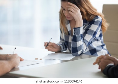 Serious millennial wife sign decree paper filing for divorce with husband visiting lawyer office, spouses end unsuccessful marriage put signature on document, man and woman get separated. Close up