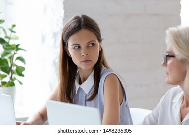 Serious millennial woman worker sit at office desk looking angry at senior colleague, grumpy young female employee feel mad dissatisfied having conflict or misunderstanding with coworker at workplace