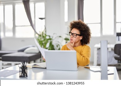 Serious mixed race attractive businesswoman dressed smart casual holding paperwork while sitting in modern office.