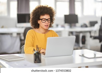 Serious mixed race businesswoman dressed casual sitting in modern office and using laptop.