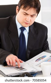 Serious modern business man sitting at office desk and working  with financial documents
