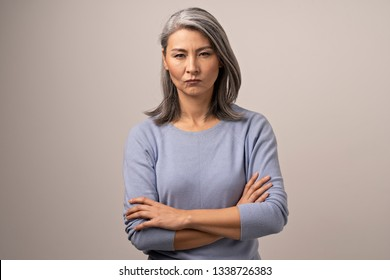 Serious Mongolian Woman with Gray Hair Against the Backdrop of Gray. The Woman Has An Evil Look. Arms Crossed She Shows Her Displeasure. Close Up Shoot.
