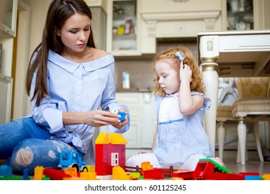 Serious mother or nanny playing with little girl
