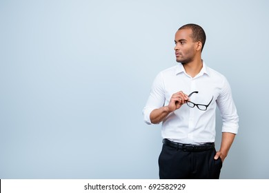 Serious mulatto american business guy is standing in formal outfit on pure blue background near the copy space, holding black glasses, looks at the copyspace
