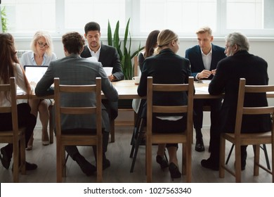 Serious multi-ethnic business people team sitting at conference table, senior executives working together with young managers at office staff meeting, focused group negotiations or teamwork concept