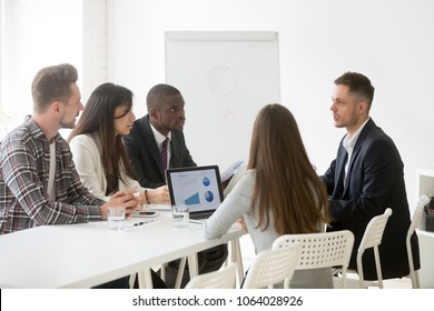 Serious multi-ethnic team listen to leader speaking at meeting, focused ceo boss coach talking to diverse surprised employees explaining solving business problem during group briefing negotiations
