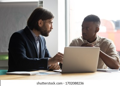 Serious multiracial male colleagues sit at office desk brainstorm talk discuss financial ideas working on laptop together, diverse coworkers cooperate at briefing using computer, collaboration concept