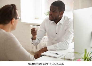Serious multiracial workers discussing business project in office, talking about company strategies and plans, African American mentor explaining new idea to Caucasian employee. Cooperation concept