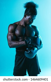 serious, muscular african american sportsman in boxing gloves posing on blue background