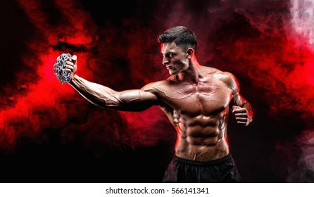 Serious muscular fighter doing the punch with the chains braided over his fist.