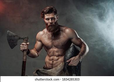 Schwere und muskulöse Reise mit Bart und nacktem Torso auf dunklem Hintergrund mit Lichtern und Rauch hält Helm und Axt.