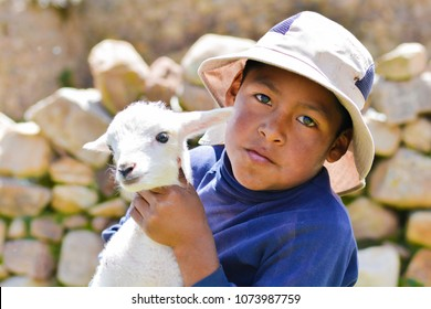 Serious native american child with a sheep.