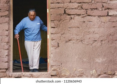 Serious native american old man with walking stick leaving his house in the countryside.