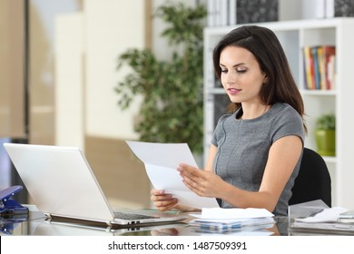 Serious office worker reading a paper letter in a desk