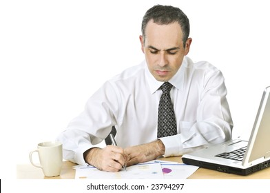 Serious office worker reviewing generic reports at his desk