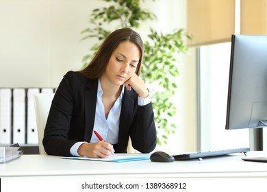 Serious office worker writing on document on a desk at workplace