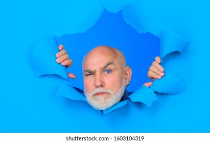 Serious old bearded man through hole in blue paper. Copy space for advertising. Discount, sale, season sales. Man through paper. Advertising.