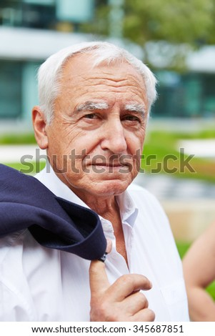 Serious old business man with white hair looking into the camera