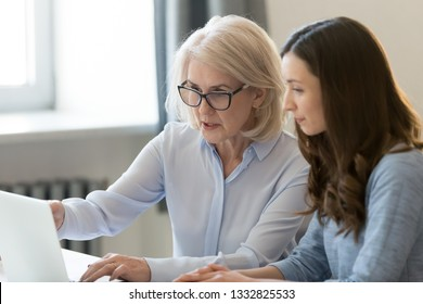Serious old female mentor teacher coach teaching intern or student computer work pointing at laptop, mature executive manager explaining online project to young employee learning new skills in office
