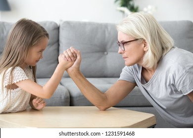 Serious old grandma and little granddaughter arm wrestling, grandchild girl and grandmother competing playing together, grandparents and children generations confrontation, family conflicts concept