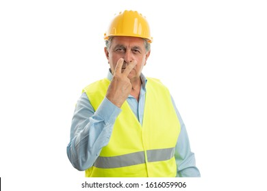 Serious old male construction worker pointing index and middle fingers at eyes as look concept isolated on white