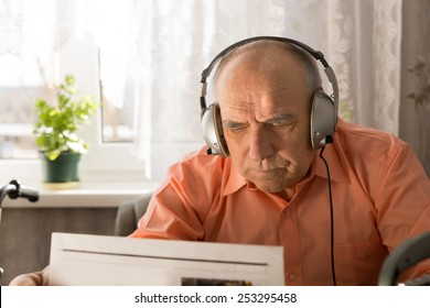 Serious Old Man with Headset Device Reading Newspaper Inside his Home.
