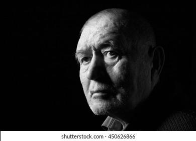 serious old man senior on black background, monochrome