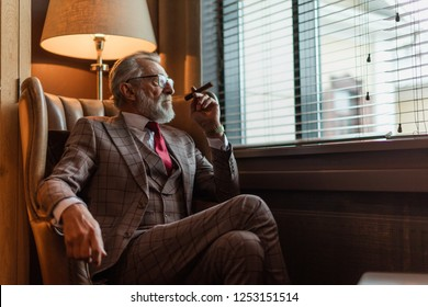 Serious old-aged businessman wearing classy custom tailored suit, red tie and expensive wristwatch sitting on old fashioned sofa in office, looking at camera and smoking cigar
