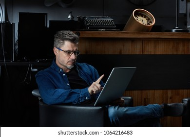 Serious older man with gray hair in casual jeans sitting in dark room using tablet, working