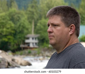 Serious ordinary caucasian male outdoors in front of a river