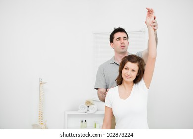 Serious osteopath raising the arm of a patient in a medical room