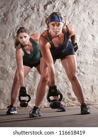Serious pair of young women lifting weights during boot camp workout
