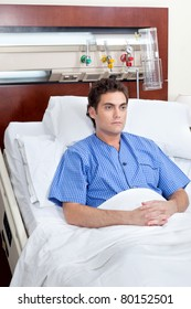 Serious patient sitting on bed in hospital