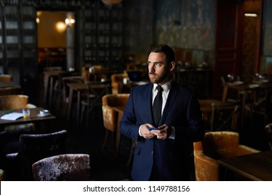Serious pensive bearded restaurant owner in formalwear standing in empty establishment and texting message while looking away