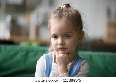 Serious pensive clever cute kid girl looking away lost in thoughts having question, smart preschool child with thoughtful face holding hand under chin dreaming, feeling curious, melancholic or bored