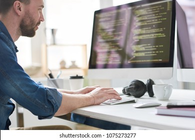 Serious pensive experienced male programmer typing code on computer while working on new software application in modern comfortable office