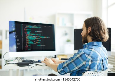 Serious pensive hipster young bearded coder in casual shirt creating computer software and working with desktop computer in modern office