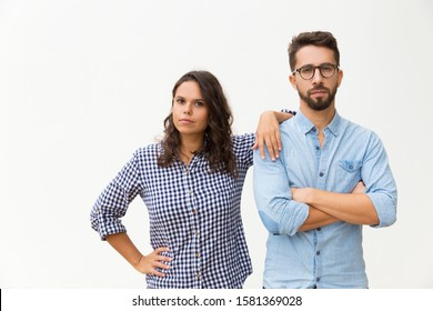 Serious pensive Latin girl leaning on boyfriend shoulder, looking at camera. Young woman in casual and man in glasses standing isolated over white background. Support and relationship concept