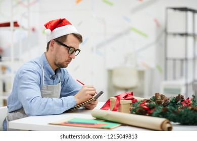 Serious pensive male designer in Santa hat and glasses sitting at table and making notes in sketchpad while working in crafting studio, he planning work and composing list of orders