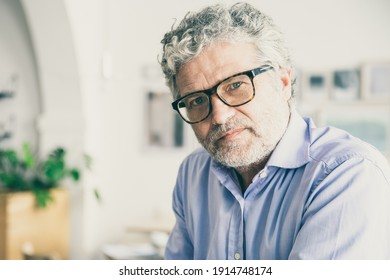 Serious pensive mature business man wearing shirt and glasses, sitting in office cafe, looking at camera. Medium shot, copy space. Business portrait concept