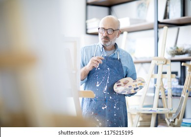 Serious and pensive mature man in apron looking at easel during creative process in studio