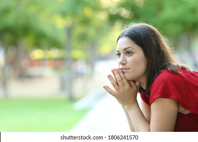 Serious pensive woman sitting on a bench in a park looks away