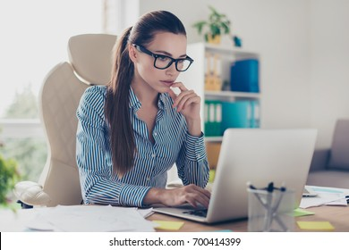 Serious pensive young business lady economist is thinking which decision to make at her modern light work place in office, wearing strict outfit and glasses