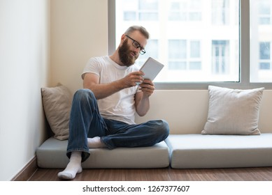 Serious pensive young man in glasses reading online article on tablet. Handsome guy sitting on sofa pillow and using modern device. Technology concept
