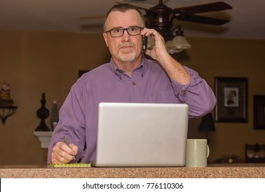 Serious phone call in home office for mature male